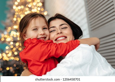 New Year. Christmas. Family. Mom and her little daughter are hugging and smiling, a Xmas tree in the background at home
