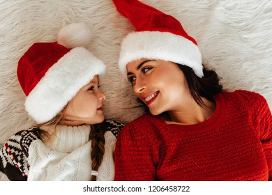 New Year. Christmas. Family. Top view of young mom and her little daughter in Santa hats looking at each other and smiling while lying on the floor at home