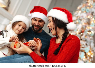 New Year. Christmas. Family. Young parents and their little daughter in Santa hats are spending time together near the Xmas tree at home