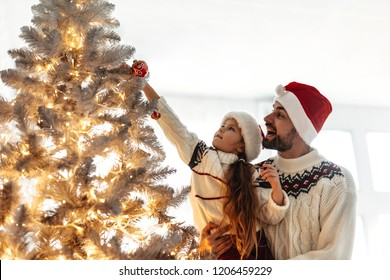 New Year. Christmas. Family. Young dad and his little daughter in Santa hats are decorating the Xmas tree at home