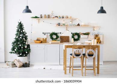 New year and Christmas. Festive Scandinavian cuisine in Christmas decorations. Candles, fir branches, wooden stands, table.