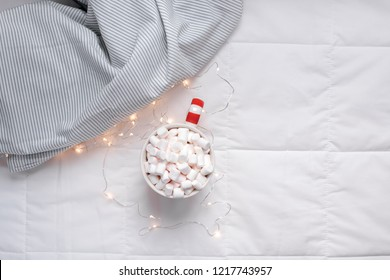 New Year or Christmas flat lay top view with Hot cacao coffee chocolate with marshmallows mug Xmas holiday celebration in bed with lights. Concept blog social media 2019