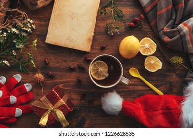New Year and Christmas flat lay top view with Santa Claus hat, gift box and cup of tea. Happy winter holidays concept.
