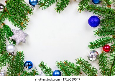 New Year and Christmas frame decoration with green fir tree branches and blue and silver shiny xmas traditional balls and baubles for greeting invitation cards isolated on white background