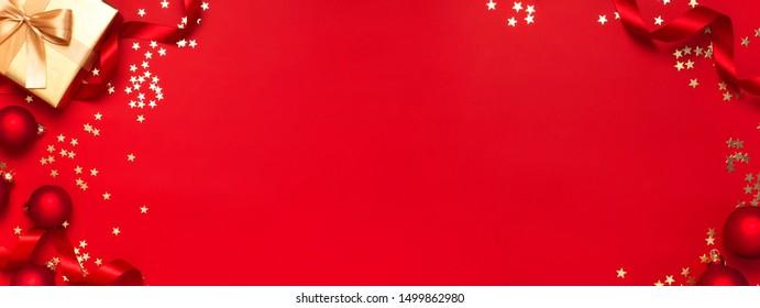 Weihnachtsgeschenke mit Band, Weihnachtsbälle, goldene Konfetti Sterne auf rotem Hintergrund Draufsicht. Flatlay Xmas Feiertag 2020 Feier. Geschenkbox Grußkarte Festliche Dekoration