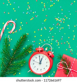 New Year or Christmas pattern flat lay top view with red alarm clock twelve midnight fir tree branch Xmas holiday celebration green paper bright colorful confetti background. Square Template text 2019