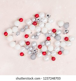New Year or Christmas pattern flat lay top view Xmas holiday celebration decorative toy balls sparkles pink concrete background copy space Template frame for greeting card your text design