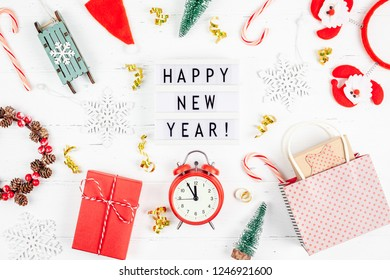 New Year or Christmas pattern flat lay top view red alarm clock twelve midnight Xmas holiday celebration white wooden golden sparkles confetti background. Template for your text design 2019