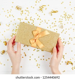 New Year or Christmas pattern flat lay top view Xmas holiday celebration decorative golden gift box sparkles white wooden background copy space Template frame for greeting card your text design
