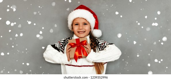 New Year. Christmas. Portrait of little girl in a Santa hat holding a gift box, looking at camera and smiling, on a gray background