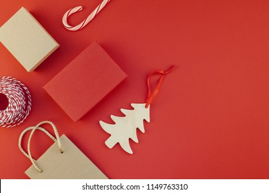 New Year or Christmas presents wrapped with ribbon flat lay top view Xmas holiday 2019 celebration handmade gift boxes on red paper background copyspace. Template mockup greeting card your text design