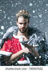 new year christmas snow concept Christmas guy in santa fur coat in crown. Drag queen, homosexual and trans. Cinderella prince with shoe on grey background. Freak, gay and transvestite. Freedom lgbt