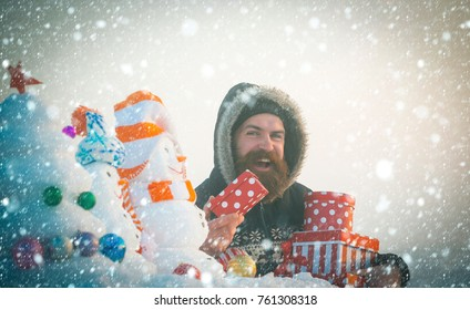 new year christmas snow concept Happy hipster with gift boxes on white sky. Snowmen and xmas snow tree on foreground. Bearded man smiling in coat with hood on head. Winter holidays concept.