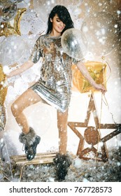 new year christmas snow concept chic and glamour, pretty happy woman or cute sexy girl in silver sequins dress has brunette hair and smiling face with golden balloons, sledge, star, feathers,