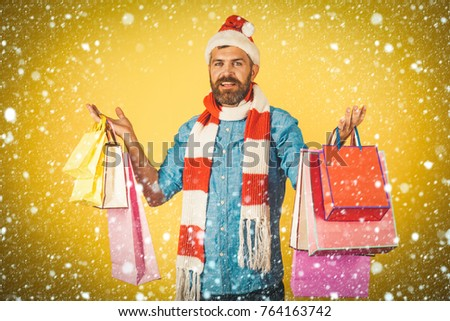 dd7980e9c6a9f new year christmas snow concept Christmas hipster shopper wear santa hat  and scarf. Black friday sale concept. Man hold shopping bags on yellow  background.
