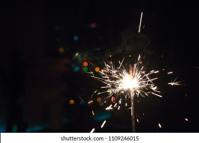 New Year Christmas sparkler on dark background with bokeh lights