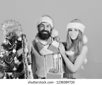 New Year and Christmas time concept. Mister and Missis Claus with red present near fir tree. Santa and sexy girl with xmas gift box. Man with beard and woman with smiling faces on red background.