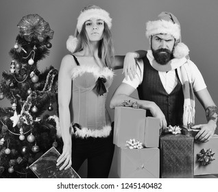 New Year and Christmas time concept. Man with beard and woman with confident faces on blue background. Santa and sexy girl in red costumes. Mister and Missis Claus with red and blue gifts near tree