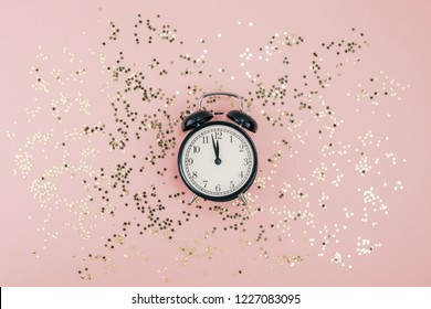 New Year Christmas Top view flat lay black alarm clock twelve covered golden stars confetti copy space millennial pink color paper background minimal style Template feminine blog social media postcard