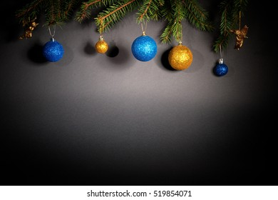 New Year. Christmas. Toys, Christmas tree branches, cones, with a cock and angels in the dark on a gray background with a blank space for text