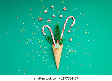 New Year Christmas Xmas holiday party celebration waffle cone candy canes fir tree branch copy space green color paper background. Template greeting card 2019