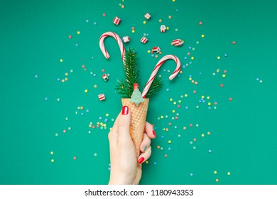 New Year Christmas Xmas holiday celebration woman hand red manicure holding waffle cone candy canes fir tree branch copy space green color paper background. Template greeting card 2019