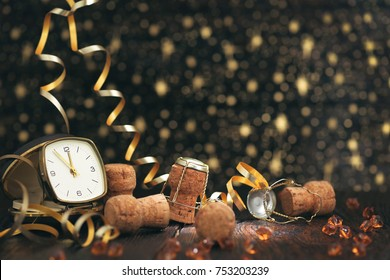 New year clock and champagne cap on wooden background. Happy New Year 2020