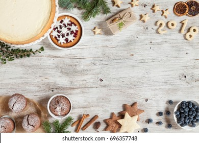 New Year composition with snowflakes, sweets, candies, cinnamon, number year 2018 on a beige wooden background.Christmass background with branches of furry spruce. Top view. Horizontal