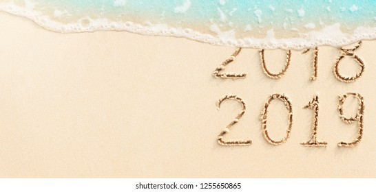 New Year concept - 2018 and 2019 handwritten on the beach with blue ocean wave on background. Place for text.