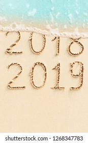 New Year concept - 2018 change to 2019. Sand beach with blue ocean wave on background.