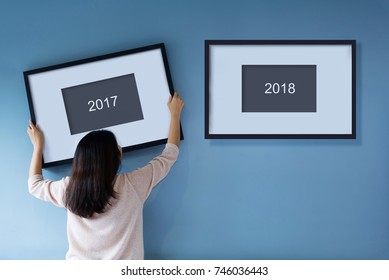 New year concept. Asian woman holding a picture frame of 2018 on blue wall. Rear view. Copy space.