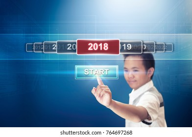 New Year Concept of A Boy Pressing or Touching the Start Button Hologram to Start the New Year 2018