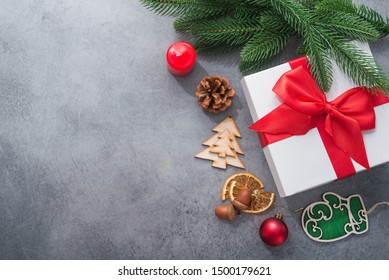 New Year concept with Christmas tree and wooden toys, red gift box on a stone background. top view. flat lay