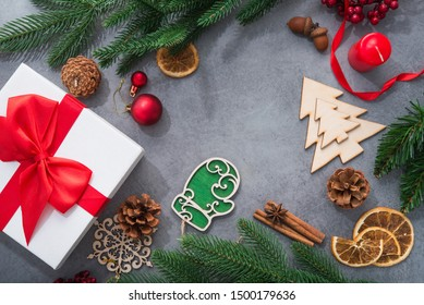 New Year concept with Christmas tree and wooden toys, red gift box on a stone background. top view. flat lay composition 2019.