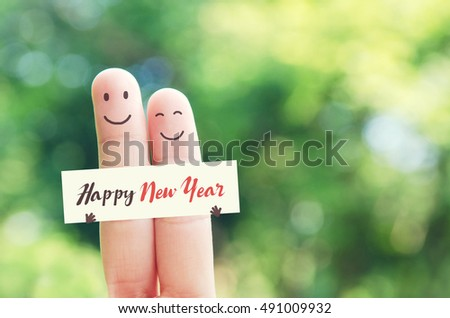 new year concept happy couple finger art holding paper with happy new year message while
