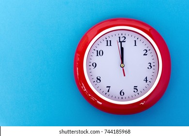 New year concept - Red wall clock pointing at 12 o'clock on blue background