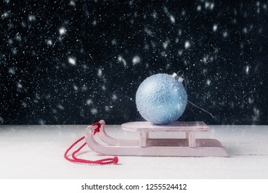 New Year concept with Santa sleigh and Christmas ball in snow-fall.