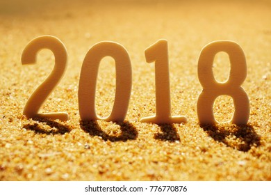 New Year Concept. Wooden numbers forming the number 2018 for new year 2018 on the golden sandy background.