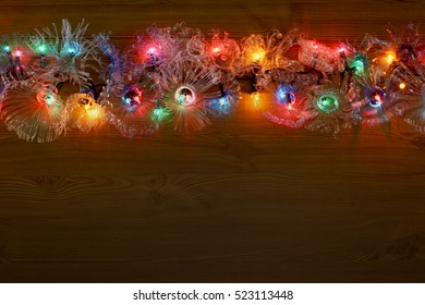New Year crafts from old plastic bottles. Traditional Christmas wreath on the door with colorful garland lights. Ecology. The idea of reusing plastic processing with copyspace.