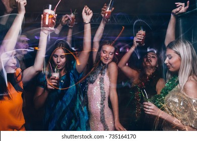 New Year dance party in night club. Happy friends company with drinks, Christmas celebration in motion. Disco people in blurred colors, modern youth life