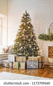New Year decorated Christmas tree in a cozy home interior near the fireplace with a clock