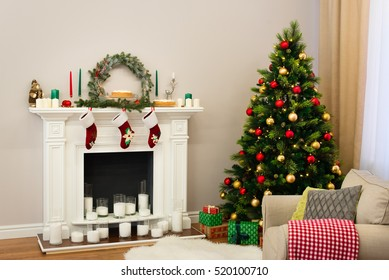 A new year decorated house with a fine tree full of colorful toys and a fireplace with candles and traditional socks hanging on it. Holiday decorated room with Christmas tree with presents under it.
