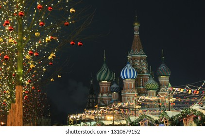 New Year decorations on the trees in Red Square and the view of the domes of St. Basil's Cathedral, the night city