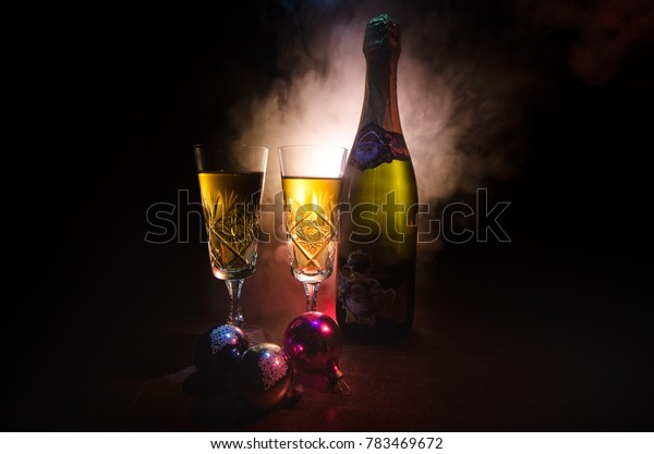 New Year Eve celebration background with pair of flutes and bottle of champagne with Christmas attributes (or elements) on snowy dark toned foggy background. Selective focus. Useful as greeting card