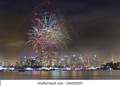 New year eve fireworks in Sydney over Harbour waters above city CBD - bright multi-colour light balls in the sky.