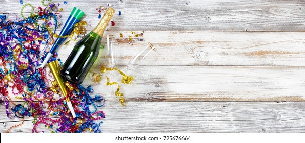 New Year eve party decorations and champagne with drinking glasses on rustic white wooden background