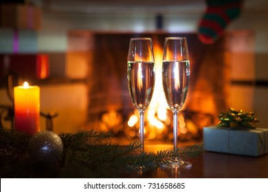 New Year. Fireplace. Two wine glasses with champagne.