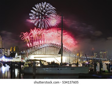 New year fireworks in Sydney over harbour, bridge and city landmarks. Giant fire balls falling down to firefall from Harbour bridge arch as seen from Lavender bay beach.
