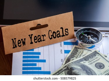 New Year Goals Words on tag with dollar note,smartphone,compass and graph on wood backgroud,Finance Concept