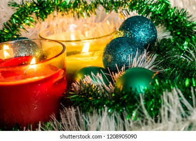 New year, green balls and decorations for the Christmas tree. Bright and beautiful scenery on a lemon background with white tinsel and beads. Christmas winter composition in the light of wax candles.